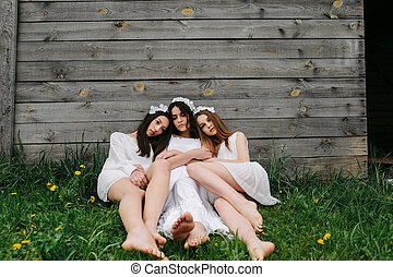 three beautiful girls on the background of a wooden house
