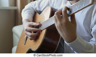 guitarist plays on acoustic guitar at home - guitarist plays...