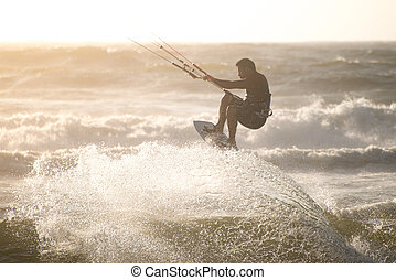 Kitesurfer jumping on a beautiful background of spray during...