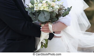 bridal bouquet of flowers in hands of the bride on wedding