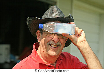 Senior holds bottle to forehead - Senior with cowboy hat...