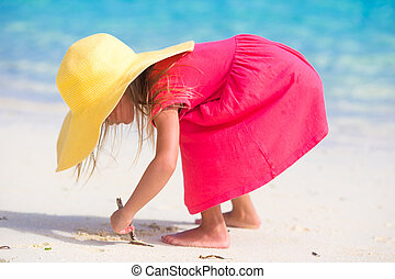 Adorable little girl in hat at beach during summer vacation...