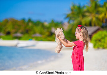 Adorable little girl playing with plush toy on beach