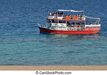Visitors on a glass boat on Coral Beach Nature Reserve in...