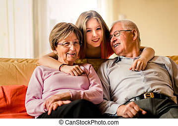 Grandchild with grandparents at home - Portrait of...