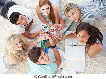 High angle of teenagers studying Science on the floor in a...