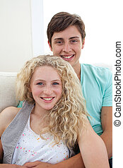 Portrait of teens couple sitting on the sofa together