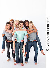 Teenagers giving their friends piggyback rides - Three...