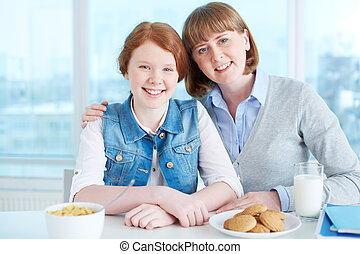 Having snack - Cute teenage girl and her mother having...