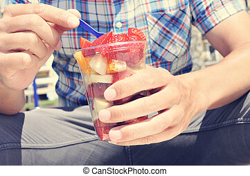 youn man eating a fruit salad outdoors