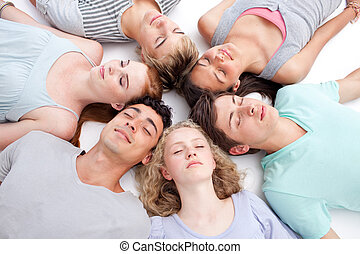 Teens lying on floor with heads together - Teens relaxing on...