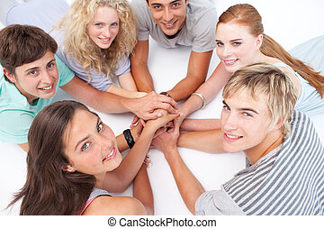 Teens playing on the floor hands games - Teenagers lying on...