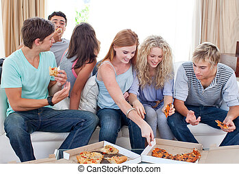 Adolescents eating pizza at home