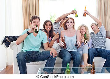 Friends drinking beer at home - Young friends drinking beer...