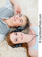 High angle of couple of teenagers listening to music on th...