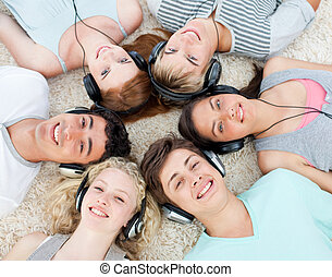 Group of teenagers listening to music - Group of young...
