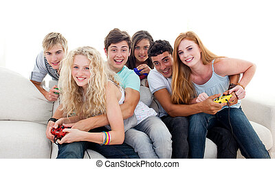 Teenagers playing video games in the living-room - Teenagers...