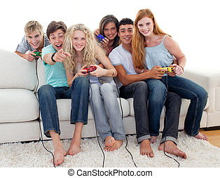Friends playing video games in the living-room - Friends...