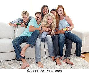 Teenagers playing video games at home