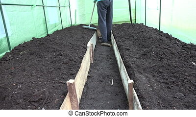 man level soil greenhouse - Farmer gardener man preparing...