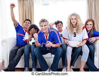 Teenagers watching a football match in the living-room -...
