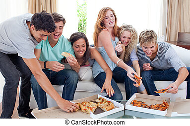 Adolescents eating pizza at home - Happy adolescents eating...