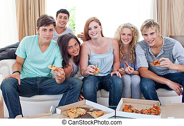 Teenagers eating pizza at home - Six teenagers eating pizza...