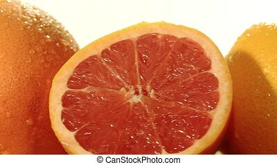 citrus fruit - orange and lemon rotating on a white...