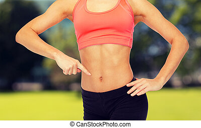 close up of woman pointing finger at her six pack - fitness,...