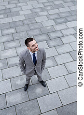 young smiling businessman outdoors from top - business,...