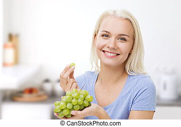 happy woman eating grapes on kitchen - healthy eating, food,...