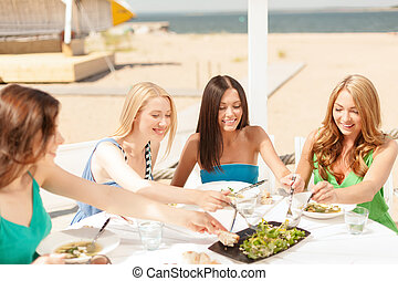 smiling girls in cafe on the beach - summer holidays and...