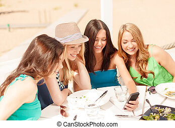 girls looking at smartphone in cafe on the beach - summer...