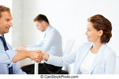 man and woman shaking hands in office - picture of...