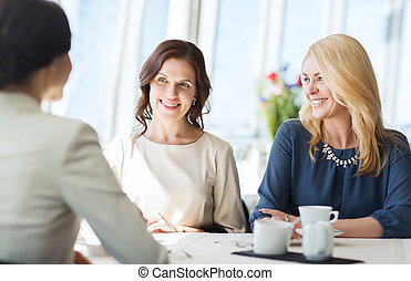 women drinking coffee and talking at restaurant - people,...