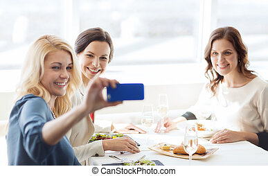 women with smartphone taking selfie at restaurant - people,...