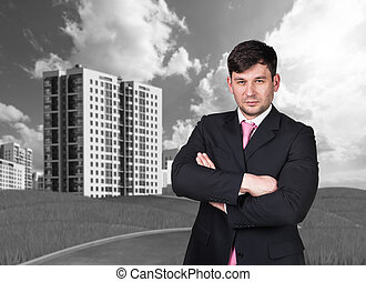Businessman outdoors looking at camera. Buildings on...