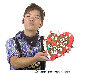 Mand holding Oktoberfest gingerbread heart and give kiss -...