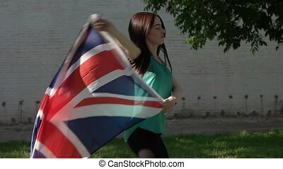 Girl dancing with union jack flag against white wall