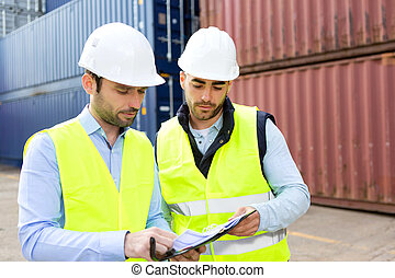 Dock worker and supervisor checking containers data on...