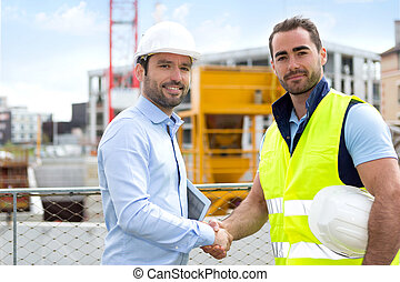 architect and worker handshaking on construction site - View...