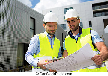 Engineer and worker checking plan on construction site -...