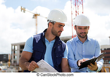 architect and worker planning meeting on construction site -...