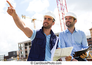Worker and architect watching some details on a construction...