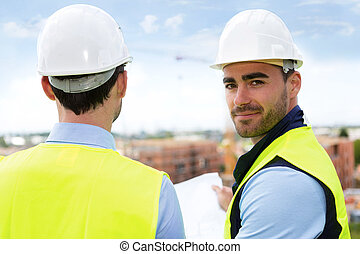 Engineer and worker watching blueprint on construction site...