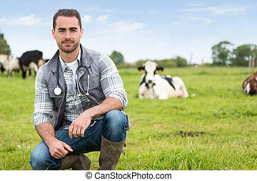 Portrait of a Young attractive veterinary in a pasture with...