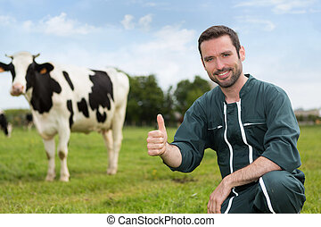 Portrait of a young attractive farmer in a pasture with cows...