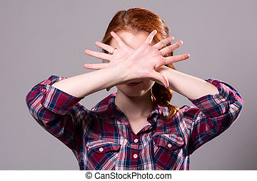 Woman with her hands signaling to stop isolated on a grey...