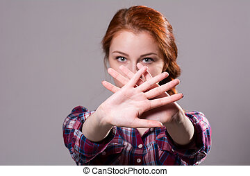 Out of focus woman with her hands signaling to stop isolated...