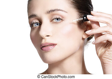 beautiful model applying a skin serum treatment  on white